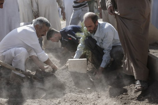Iraq_Bassam Hussein, 44, buries his ten-year-old son who was killed by a roadside bomb deep in Kurdish territory near Rabiaa_Picture_Sam_Tarling:The Telegraph