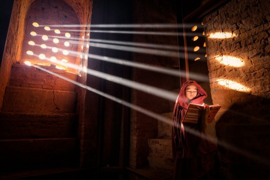 LightSource. Young Monk finds a perfect light source to read his book inside of his pagoda - Old Bagan, Burma—Marcelo Castro