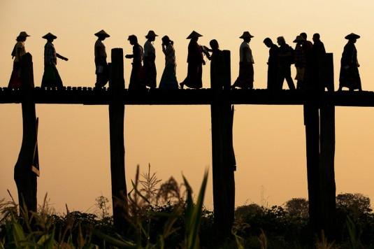 U Bien Bridge Crossing. Locals, monks, kids, tourists, all walking on U Bien bridge made out of teakwood, in Amarapura, South of Mandalay, Myanmar—April Badilles
